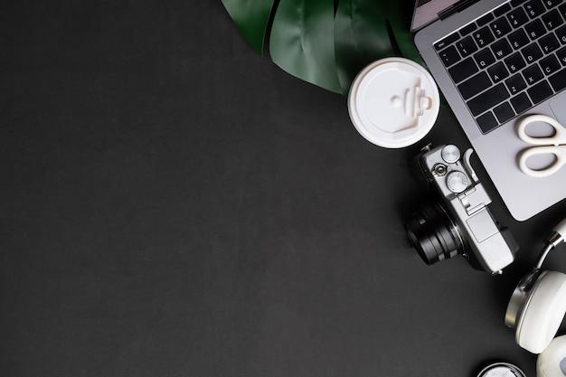 Mesa de artista computador, câmera, café e fones de ouvido na mesa preta com vista superior