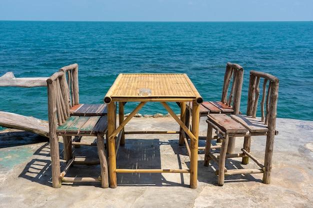 Mesa de bambu e cadeiras de madeira no café vazio ao lado da água do mar em uma praia tropical. fechar-se. ilha de koh phangan, tailândia