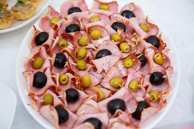 Mesa de banquete bem decorada com diversos petiscos e sanduíches de aperitivos