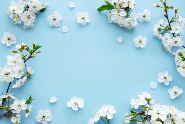 Mesa de borda de primavera com lindos ramos de flores brancas. mesa azul, floresce delicadas flores. conceito de primavera. espaço da cópia da vista superior plana leiga.
