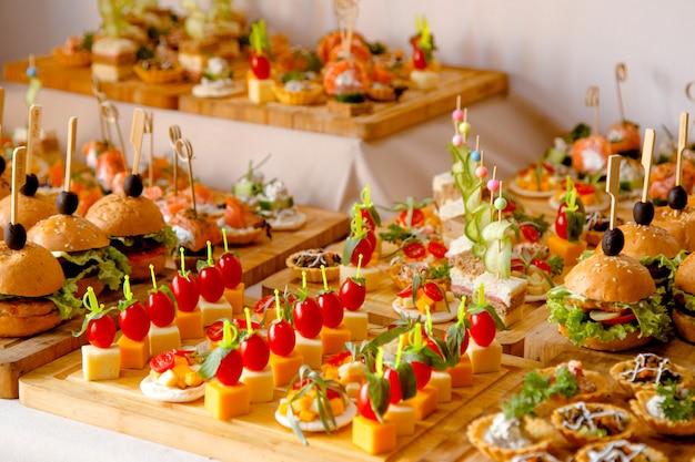 Mesa de buffet com lanches de queijos hambúrgueres etc