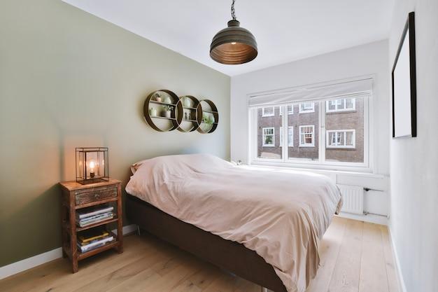 Mesa de cabeceira retrô com livros e abajur perto de uma cama confortável e prateleira com decorações contra a janela em um quarto moderno