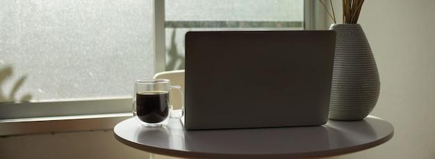 Mesa de café branca com laptop aberto, caneca de café e vaso de flores ao lado da janela