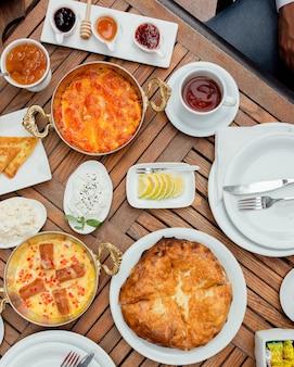 Mesa de café com variedade de alimentos e xícara de chá.