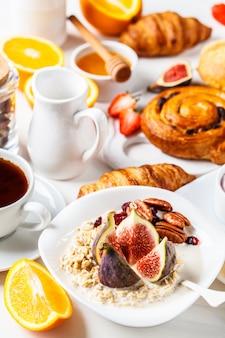 Mesa de café da manhã com aveia, croissants e frutas.