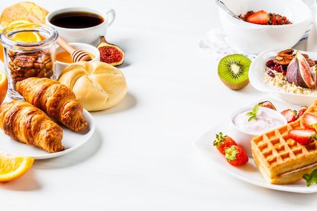 Mesa de café da manhã com aveia, waffles, croissants e frutas.