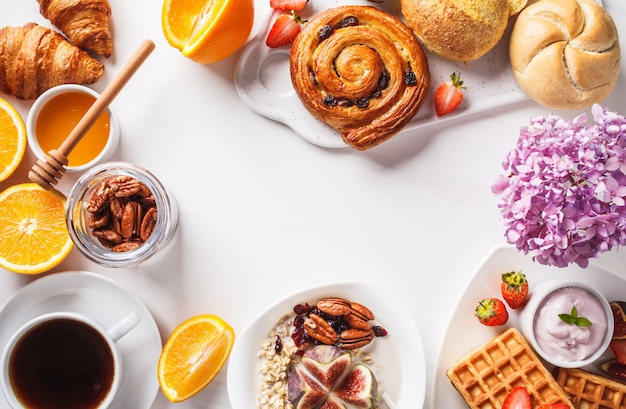 Mesa de café da manhã com aveia, waffles, croissants e frutas