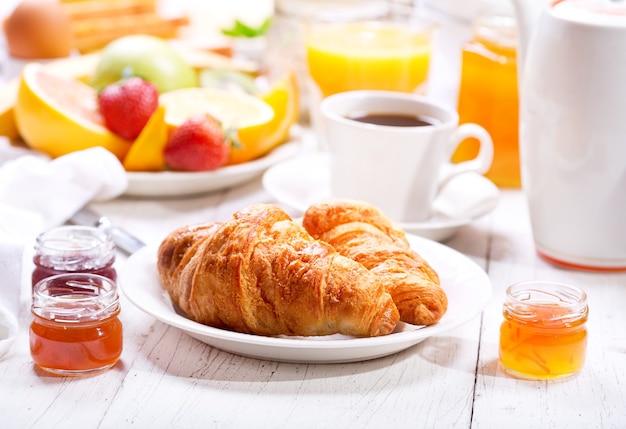 Mesa de café da manhã com croissants, café, suco de laranja, torradas e frutas