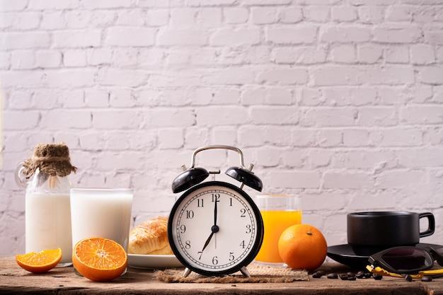 Mesa de café da manhã com despertador clássico e café da manhã.