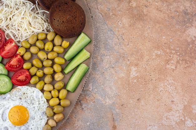Mesa de café da manhã com fatias de pão, vegetais e ovo