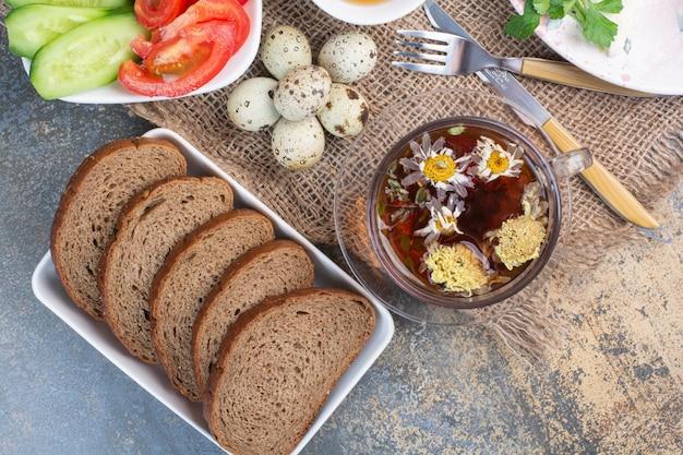 Mesa de café da manhã com legumes, chá, pão e ovos na serapilheira.