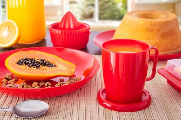 Mesa de café da manhã com mamão, laranja, bolo, frutas e pão.
