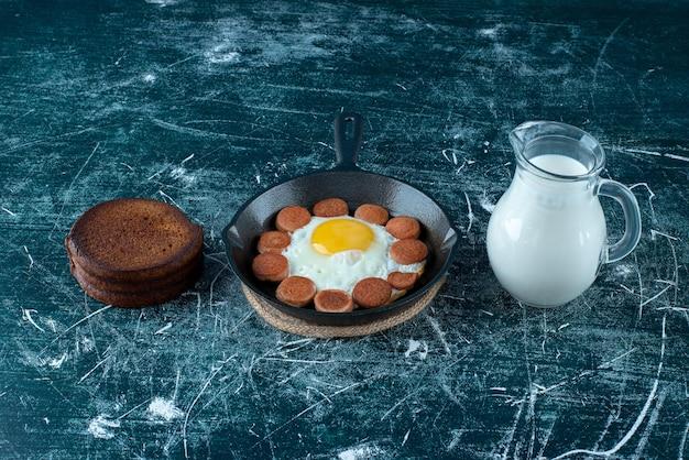 Mesa de café da manhã com ovos fritos, salsichas e panquecas.