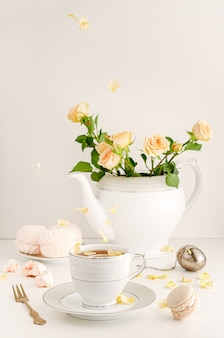 Mesa de café da manhã com rosas, pétalas, macaron e merengues