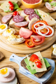 Mesa de café da manhã com sanduíches de queijo, linguiça, legumes, ovos cozidos e frutas. vista do topo