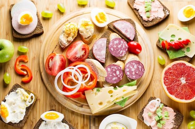 Mesa de café da manhã com sanduíches de queijo, lingüiça, legumes, ovos cozidos e frutas