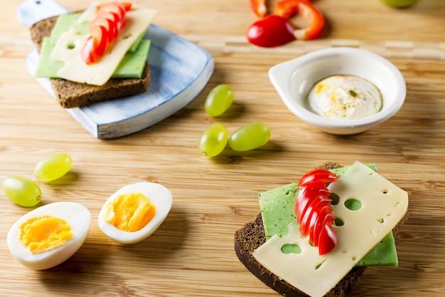 Mesa de café da manhã com sanduíches de queijo, ovos cozidos e frutas. vista do topo
