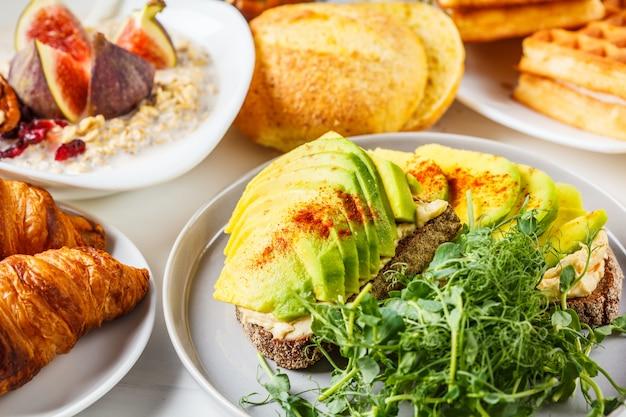 Mesa de café da manhã com torradas de abacate, aveia, waffles, croissants em fundo branco.