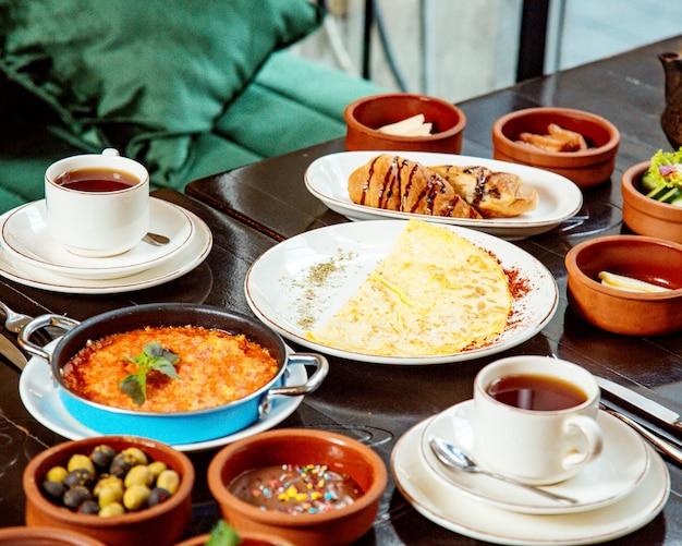 Mesa de café da manhã com xícaras de chá de azeitonas e omelete