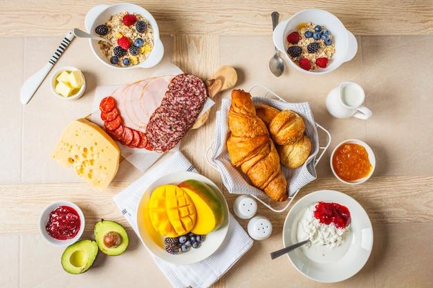 Mesa de café da manhã continental com croissants, geléia, presunto, queijo, manteiga, granola e frutas.