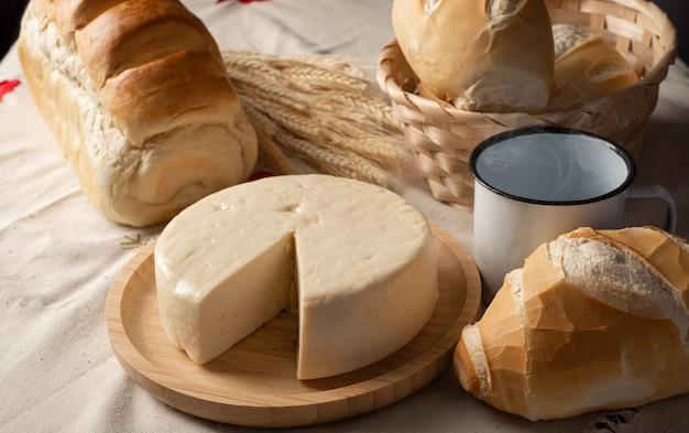 Mesa de café da manhã no brasil com pães, queijos, xícara de café e acessórios sobre uma toalha leve com bordados.