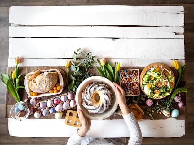 Mesa de café da manhã ou brunch repleta de ingredientes saudáveis para uma deliciosa refeição de páscoa com amigos e familiares ao redor da mesa. o conceito de férias da páscoa e os valores familiares.