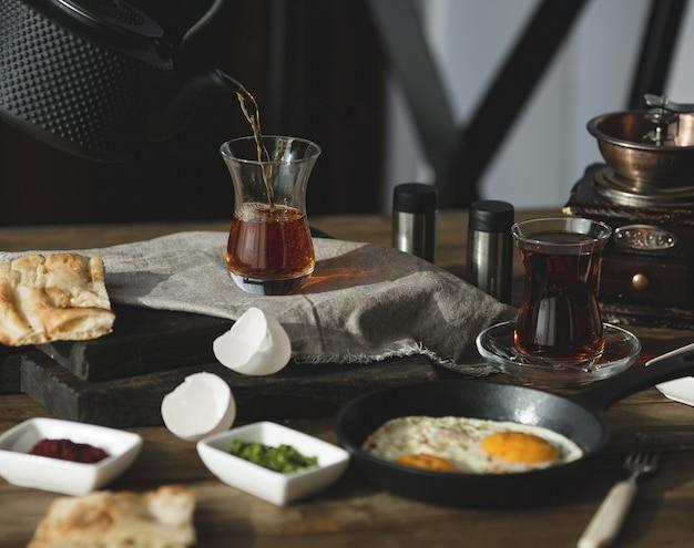 Mesa de café da manhã para duas pessoas com copos de chá e ovos fritos