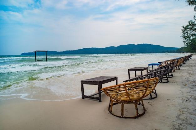 Mesa de café de madeira e cadeiras em uma praia tropical com mar azul no fundo. ilha de koh rong samloem, baía saracen. camboja.