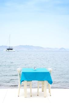 Mesa de café servida com uma toalha de mesa azul perto da costa do mar para umas férias relaxantes