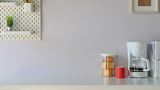 Mesa de canto de café no escritório com máquina de café, caneca, lanche, placa de peg na mesa branca.
