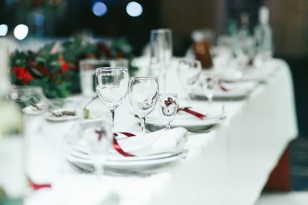 Mesa de casamento ajustada com guardanapos brancos e fitas vermelhas