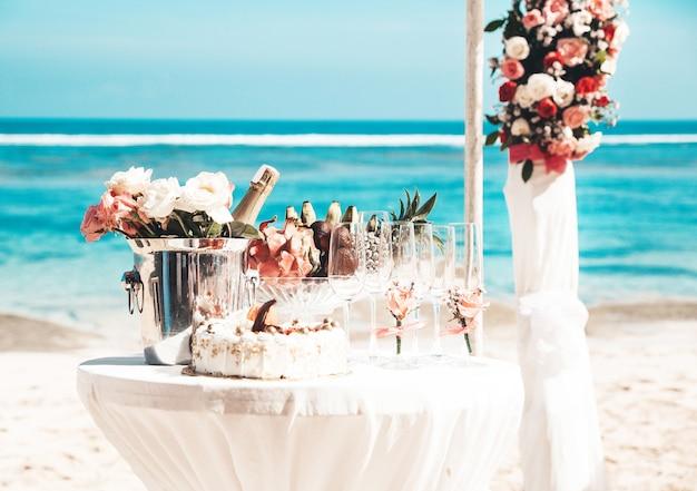 Mesa de casamento elegante com frutas tropicais e bolo na praia