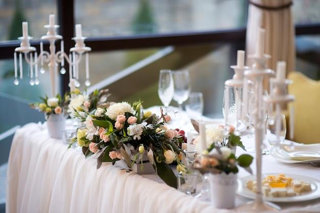 Mesa de casamento primorosamente decorada com buquê de flores.