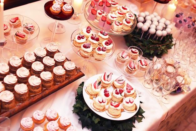 Mesa de catering com bolos de chocolate fatiados, decorados com framboesas frescas e nozes.