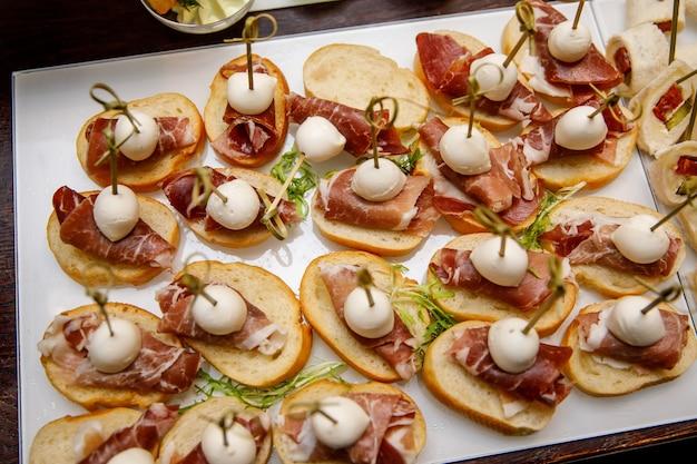 Mesa de catering definir serviço vários lanches em uma mesa de banquete. conjunto de lanches frios, canapés, bebidas, closeup.