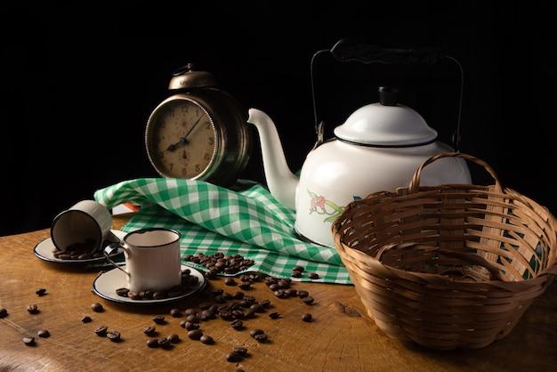 Mesa de centro com relógio antigo, xícaras, grãos de café e pão de queijo em madeira rústica, com toalha xadrez verde e branca, foco seletivo.