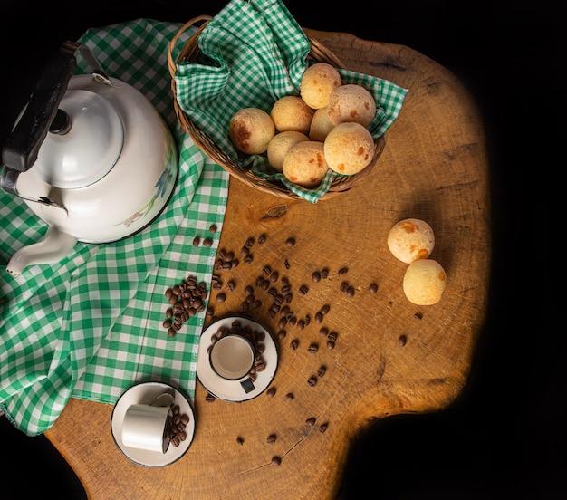 Mesa de centro com relógio antigo, xícaras, grãos de café e pão de queijo em madeira rústica, com toalha xadrez verde e branca, vista de cima.