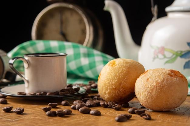 Mesa de centro no brasil em detalhe com relógio antigo, xícaras, grãos de café e pão de queijo em madeira rústica, com toalha xadrez verde e branca, foco seletivo.