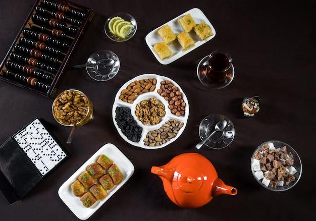 Mesa de chá com copos de chá, nozes e jogos de azar.