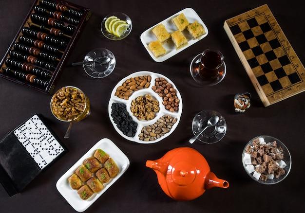 Mesa de chá com copos de chá, nozes e placas de jogos.
