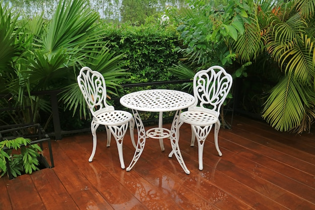 Mesa de chá de jardim de ferro forjado branco vazio e cadeiras no pátio depois da chuva