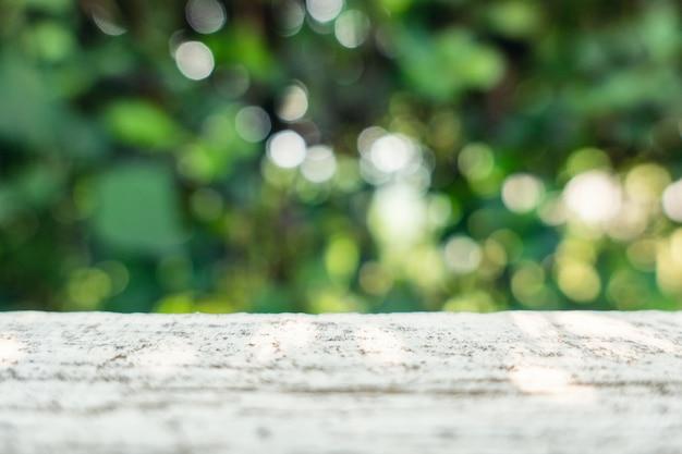 Mesa de cimento com a planta verde turva com bokeh no jardim