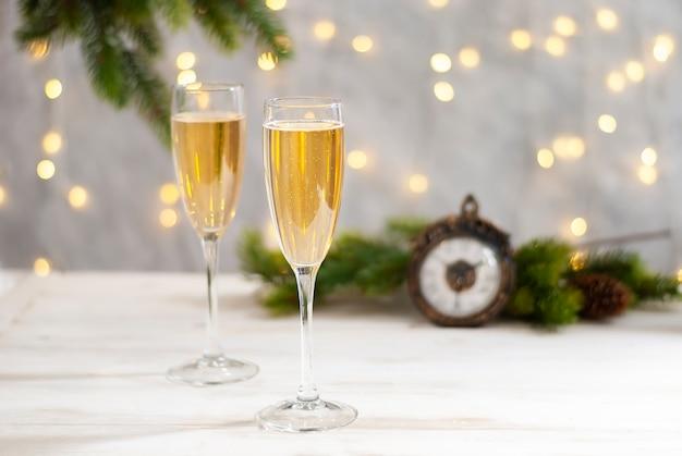 Mesa de comemoração de ano novo e feriado de natal com duas taças com champanhe