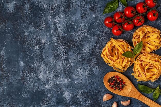 Mesa de comida italiana com macarrão, temperos e legumes.