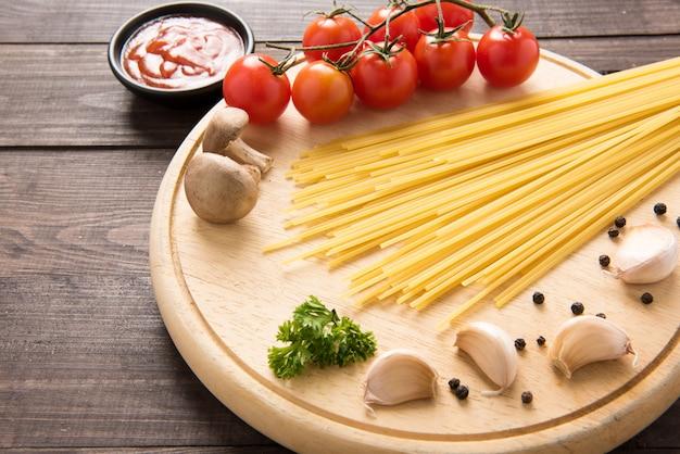 Mesa de comida italiana, com tomate, alho, pimenta, espaguete e cogumelos mesa de madeira