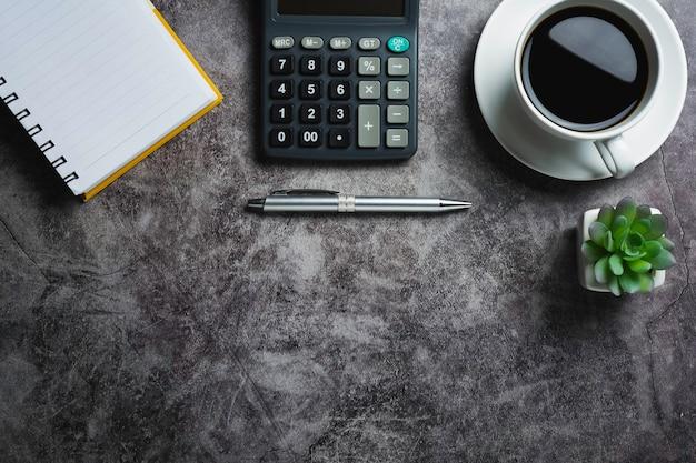 Mesa de concreto com café com acessórios de escritório. vista superior da xícara de café na mesa de concreto