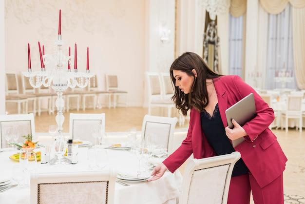 Mesa de configuração de gerente de banquete feminino para evento