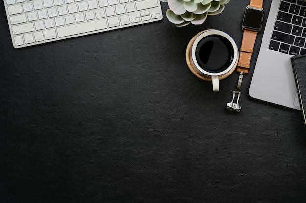 Mesa de couro escura com gadget de escritório em casa e espaço de cópia.