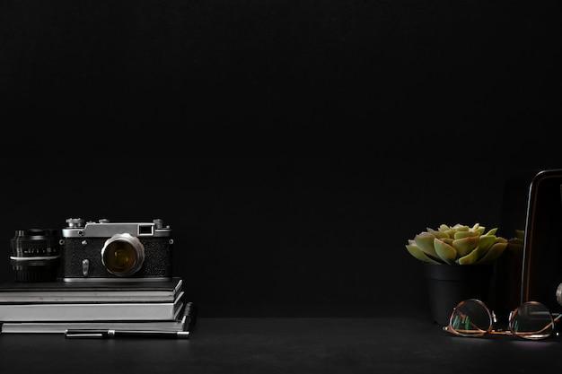 Mesa de couro escuro com câmera vintage, material de escritório em casa e espaço de cópia