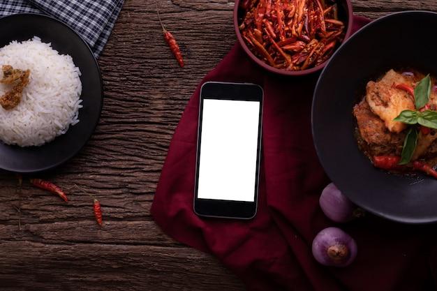 Mesa de cozinha com a tela vazia no telefone esperto, na tabuleta, no telefone celular e no caril vermelho secado do coco da carne de porco.